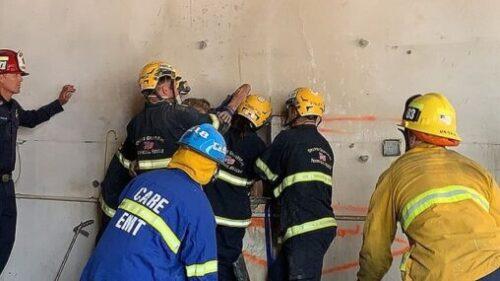 壁の間に挟まれた全裸の女性を救助